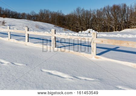 wooden fence on winter farming field in nice day