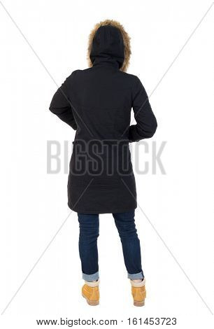 Back view woman in winter jacket  looking up.   Standing young girl in parka. Rear view people collection. Girl in a black winter jacket with a hood to hide his hands in his pockets
