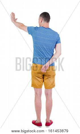 back view of man. Young man in shorts presses down on something. Isolated over white background. Rear view people collection. backside view of person. she holds his hand open, palm forward