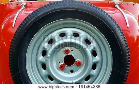 Spare tire on back of red vintage car