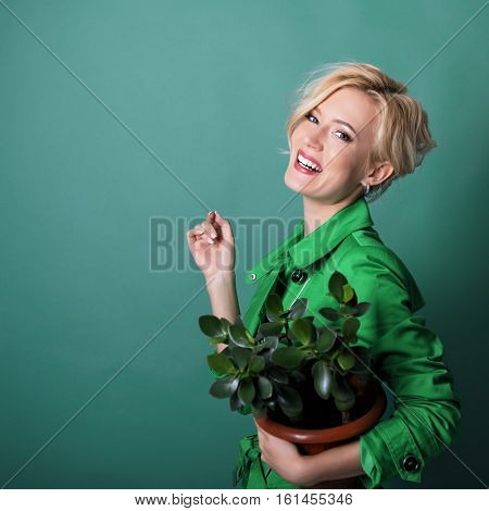 Young happy smiling woman holding flowerpot with fresh plant over green background. Conservationist.