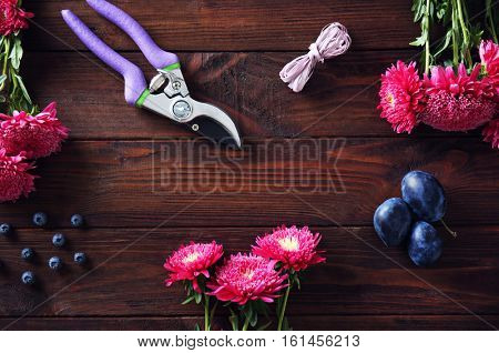 Beautiful flowers, berries and plums for composition on wooden background