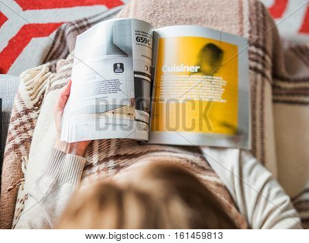 PARIS FRANCE - AUGUST 24 2014: View from above of woman reading IKEA Catalogue before buying kitchen furniture for her new house. The catalogue is published annually by the Swedish home furnishing retailer