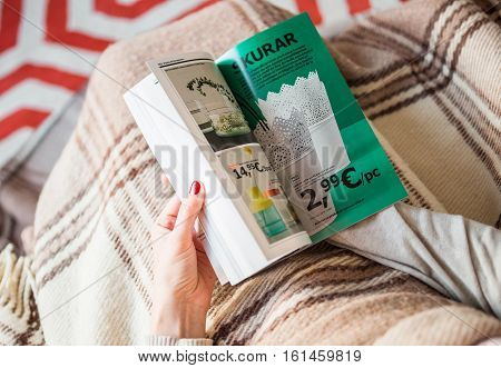 PARIS FRANCE - AUGUST 24 2014: Busy woman reading IKEA Catalogue before buying furniture for her new house. The catalogue is published annually by the Swedish home furnishing retailer