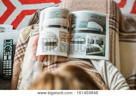 PARIS FRANCE - AUGUST 24 2014: View from above of woman reading IKEA Catalogue before buying bedding and bedroom furniture for her new house. The catalogue is published annually by the Swedish home furnishing retailer
