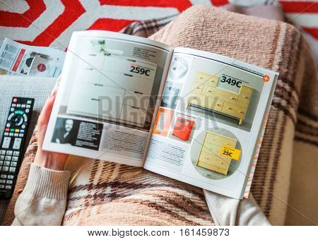 PARIS FRANCE - AUGUST 24 2014: View from above of woman reading IKEA Catalogue before buying commode storage furniture for her new house. The catalogue is published annually by the Swedish home furnishing retailer
