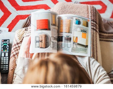 PARIS FRANCE - AUGUST 24 2014: View from above of woman reading IKEA Catalogue before buying new commode furniture for her new house. The catalogue is published annually by the Swedish home furnishing retailer