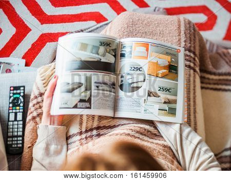 PARIS FRANCE - AUGUST 24 2014: View from above of woman reading IKEA Catalogue before buying bedroom furniture for her new house. The catalogue is published annually by the Swedish home furnishing retailer