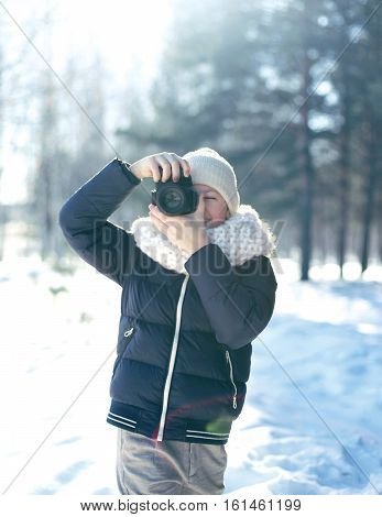 Child little boy photographer takes picture on the digital camera outdoors in winter sunny day over blurred forest background