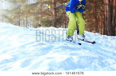 Winter Skier Teenager In Sportswear Skiing Over Snow At Sunny Forest Background
