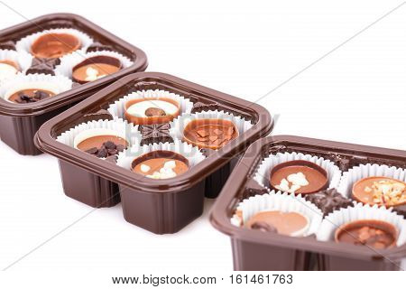 Assortment of chocolate in plastic boxes on white background.
