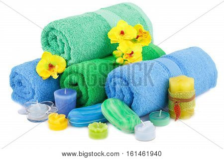 Spa set with towels candles and flowers isolated on white background.