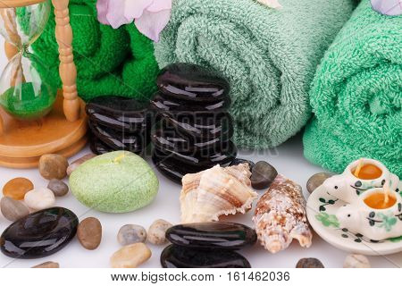 Spa set with towels candles shells sandglass and stones closeup picture.