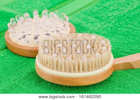 Wooden massagers on green towel closeup picture.