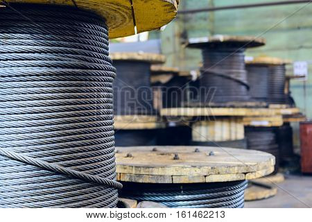 Large cable reels stocked in the factory premises. Workshop production of cable slings.