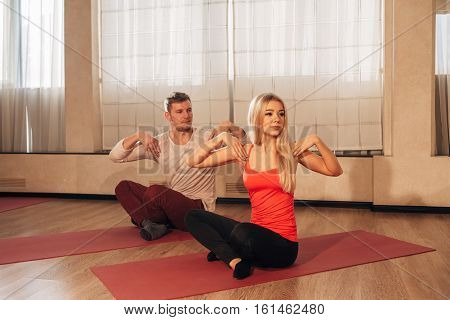 man and woman doing Yogi body twisting in the ballroom