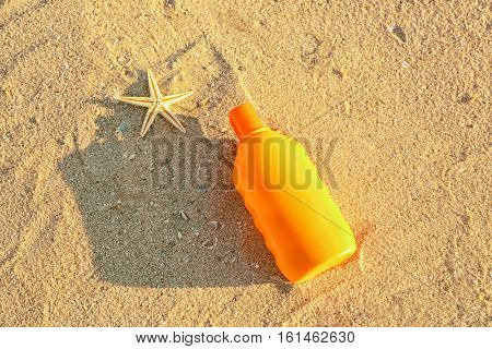 Sunscreen cream and starfish on sea coast, close up view