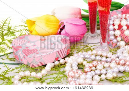 Two glasses flowers colorful pearls necklaces and gift box on white background.