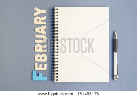 Top view of spiral open notebook with pen and February month wording on grey background