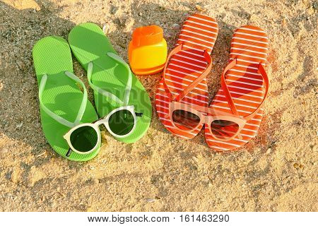 Sunglasses, sandals and sunscreen cream on sea coast