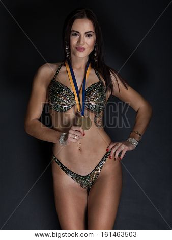beautiful woman bodybuilder with medals on a black background
