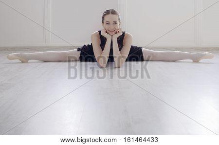 Classical Ballet dancer portrait. Beautiful graceful ballerine in black practice split ballet position in class room background. Ballet class training, copy space on floor