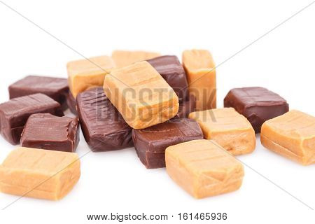 Heap of caramel candies on white background.