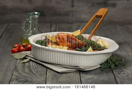 Baked chicken legs with lemon and thyme in a baking dish on the wooden table