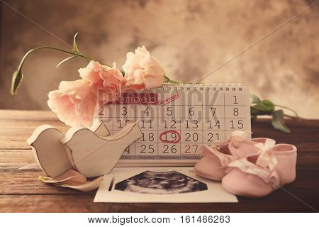 Calendar with mark, ultrasound picture of baby and children shoes on table