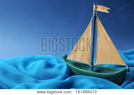 Wooden boat and cloth on blue background. Columbus Day concept