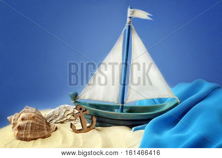 Wooden boat, shell and anchor on blue background. Columbus Day concept