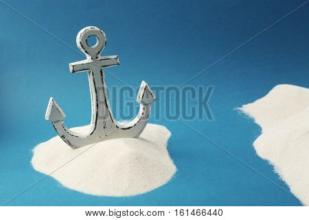 Old anchor in sand on blue background. Columbus Day concept