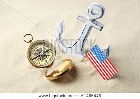 Anchor, compass and USA flag in sand. Columbus Day concept