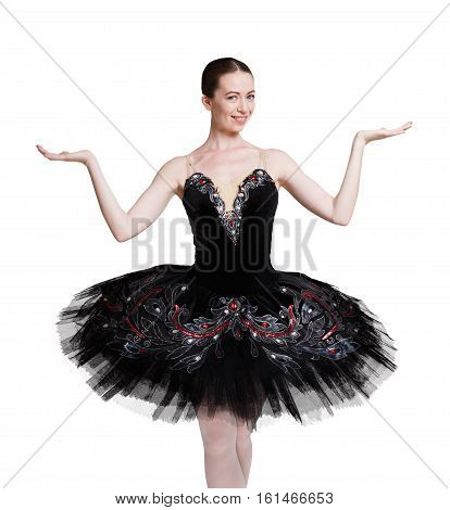 Classical Ballet dancer. Beautiful graceful ballerine practice ballet positions in black swan tutu dress, shows something with open hands. Portrait isolated on white background