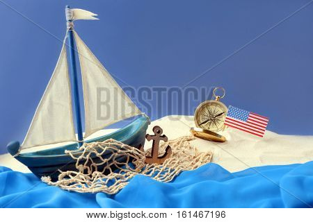 Wooden boat, compass and USA flag on blue background. Columbus Day concept