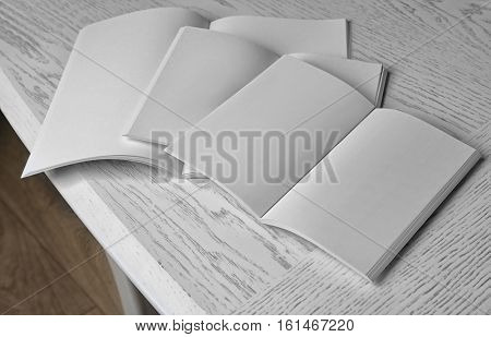 Blank open brochures on wooden table