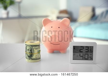 Savings concept. Piggy bank with money and electronic thermometer on table