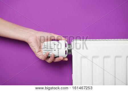 Female hand on temperature regulator of heating battery on pink background, closeup