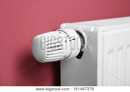 Heating radiator with temperature regulator on pink background, closeup