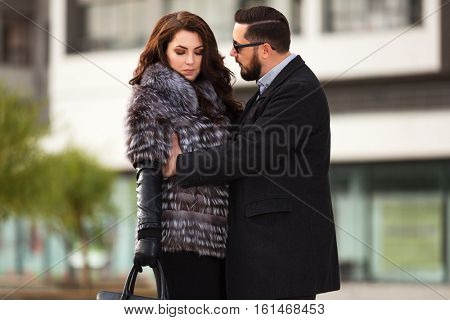 Young couple in conflict on city street. Stylish fashion model outdoor