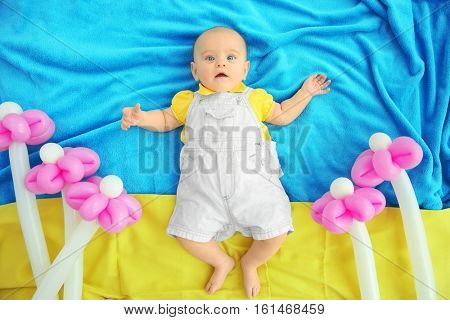Cute baby lying on bedspread among flowers made of balloons