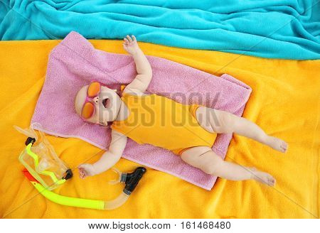 Cute baby with snorkeling mask, towel and sunglasses lying on colorful bedspread. Holidays at sea with baby, concept