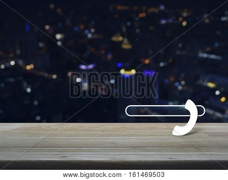 Phone icon with copy space for add your phone number on wooden table over blur colourful night light city tower background Contact us concept