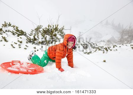 Beautiful girl enjoying winter and snow playing with plastic saucer sled falling in the snow. Active family lifestyle outdoor and natural childhood carefree childhood concept.