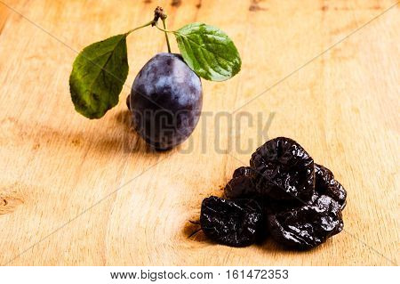 Healthy food good cuisine. Closeup dried plums and fresh prune fruit on wooden rustic table