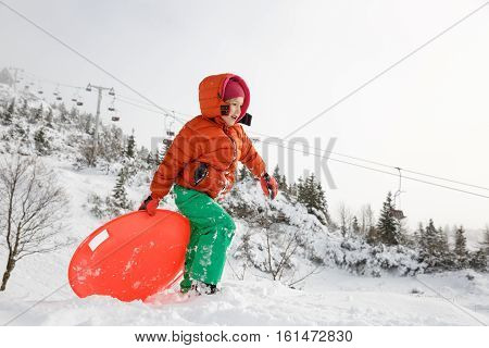 Beautiful girl enjoying winter and snow playing with plastic saucer sled ski lifts in the back. Active family lifestyle outdoor and natural childhood carefree childhood concept.
