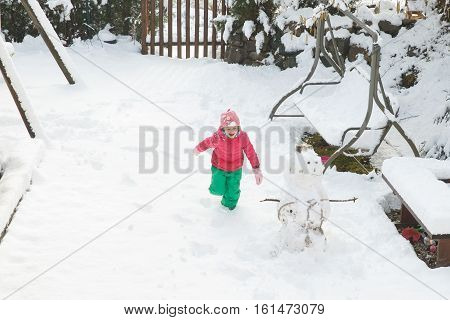 Playful girl running playing in home backyard with snow building a snowman having fun and being active. Natural lifestyle and free childhood concept with copy space.
