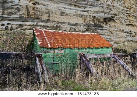 derelict green rusty metal wooden shed shack at bottom of cliffs