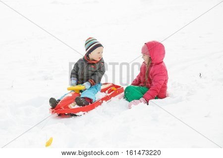 Brother and sister playing in the snowy winter landscape boding sledding having winter fun. Active family lifestyle outdoor and natural childhood fun and carefree childhood concept.