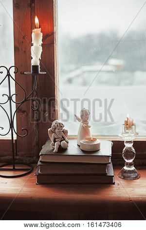 Warm and comfy winter concept. Book and candlestick on wooden window sill in old house. Reading and relaxing in cold snowy weather at home. Quiet silent homely scene.